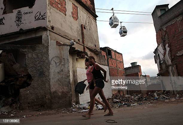 Cable cars ferry passengers as pedestrians walk in the streets of the Complexo do Alemao favelas in Rio de Janeiro Brazil on Friday Aug 26 2011 A...