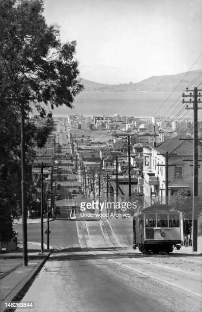 Cable cars on the Fillmore Street hill looking down at the Marina with Angel Island in the background San Francisco California circa 1920