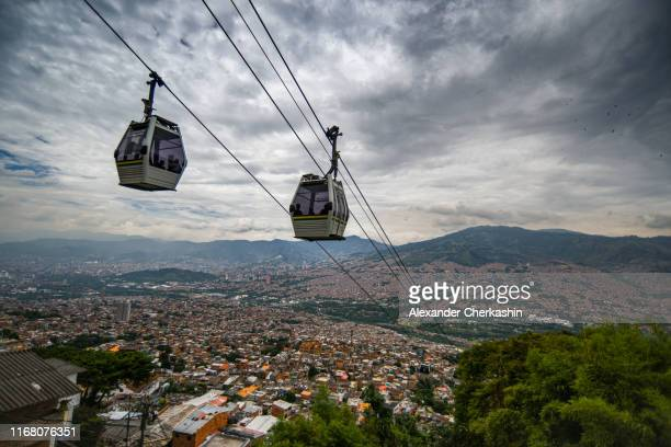 cable cars on top of medellin city in cloudy weather - medellin colombia stock pictures, royalty-free photos & images