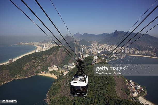 Cable cars taking tourists and sightseers to and from the top of Sugar Loaf Mountain one of the iconic tourist destinations in Rio de Janeiro Rio de...
