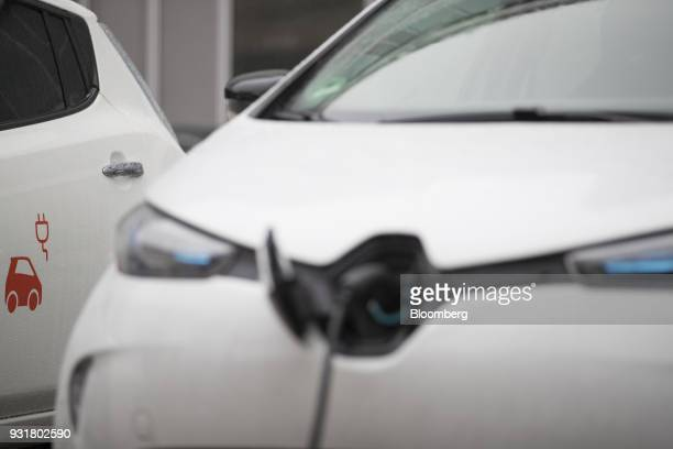 A cable charges an electric automobile at a charging station outside the headquarters of EON SE in Essen Germany on Tuesday March 13 2018 EON will...