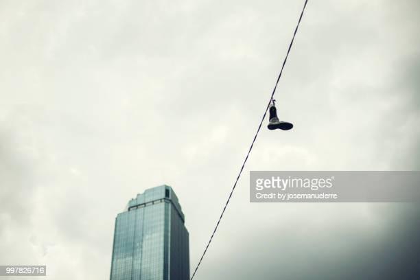 cable con zapatillas colgando frente a un gran edificio azul - josemanuelerre fotografías e imágenes de stock