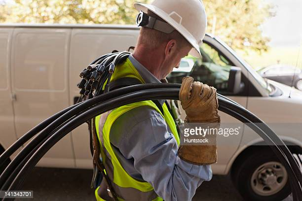 cable installer carrying video cables from a truck - maintenance engineer stock pictures, royalty-free photos & images