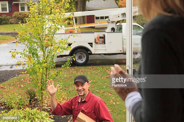 Cable installer leaving and waving to homeowner
