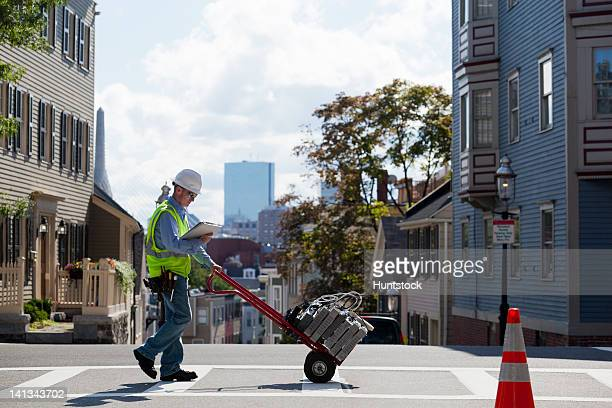 cable installer with hand truck full of set-top boxes in the city - power occupation stock photos and pictures