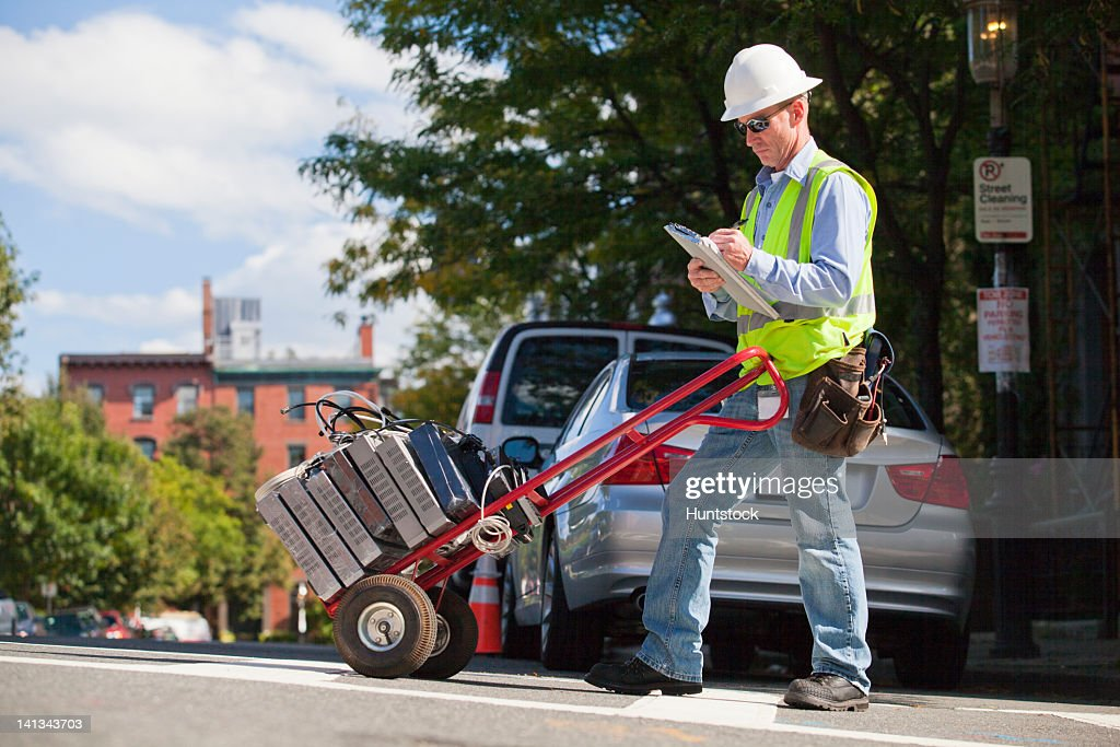 Cable installer with hand truck full of set-top boxes in the city logging data : Stock Photo