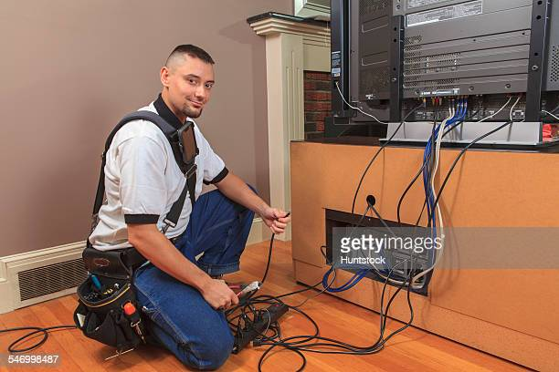 Cable installer working in a home behind the TV