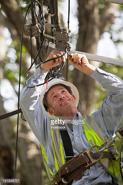 Cable installer working on residential connections at utility pole installing a filter