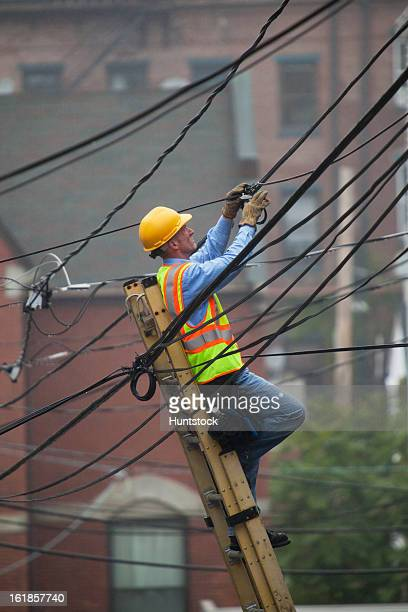 Cable lineman assessing cable splice in the city from ladder