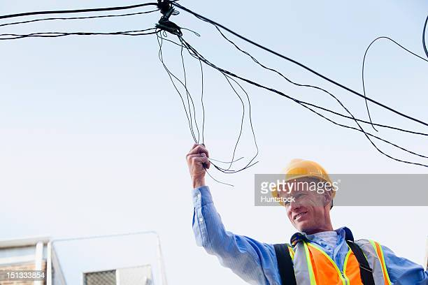 Cable lineman on ladder fixing dangling wires