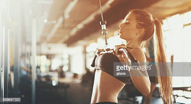 cable pull downs at a gym. - extra long stock pictures, royalty-free photos & images