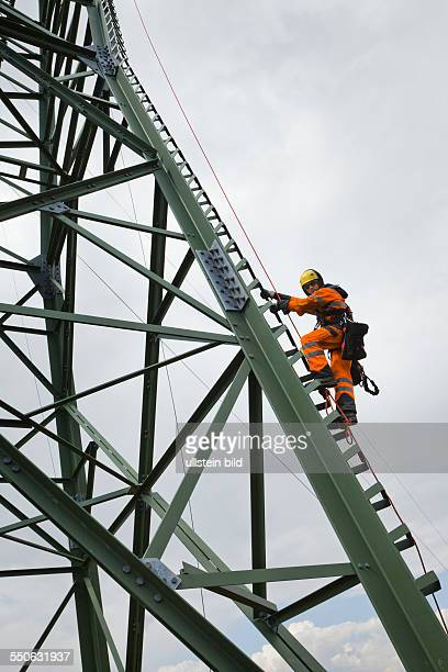 Cable riggers escalating a newly built transmission tower that is run by transmission system operator 50Hertz