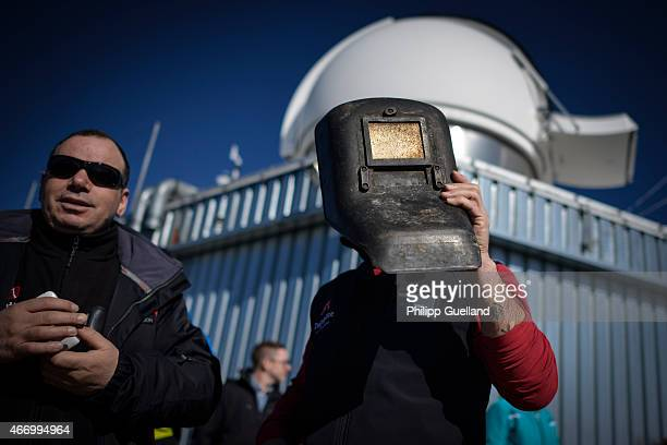 A cablecar worker on Zugspitze mountain uses a welding mask to look into the sky at a partial solar eclipse on March 20 2015 in GarmischPartenkirchen...