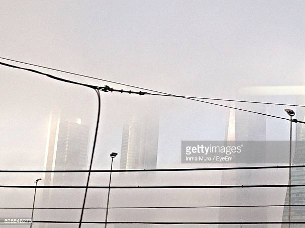 cables and street light against buildings - muro stock photos and pictures