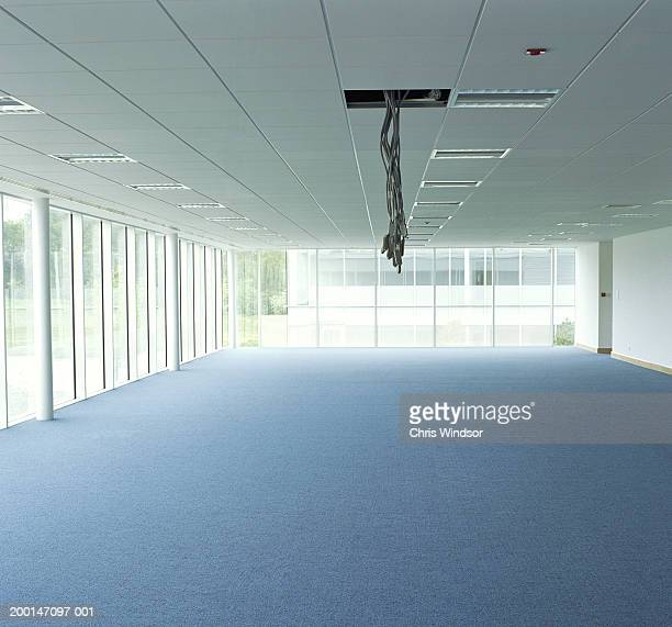 Cables hanging from gap in ceiling in empty office