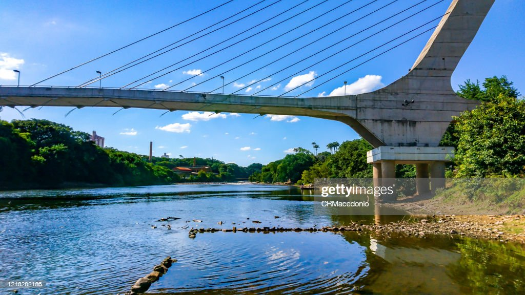 Cable-stayed bridge over the Piracicaba River in a dry season, under blue sky between clouds. : Stock Photo