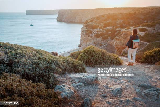 cabo sao vicente, sagres. tourist girl watching the bay at sunset. portugal - iacomino portugal foto e immagini stock