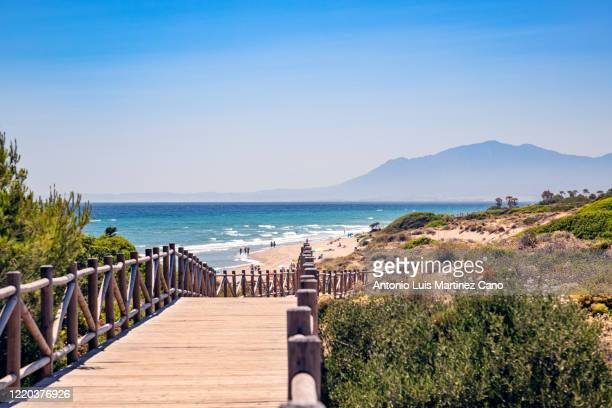 cabopino beach in the municipality of marbella, malaga. wooden walkway to the beach. - málaga málaga province stock pictures, royalty-free photos & images