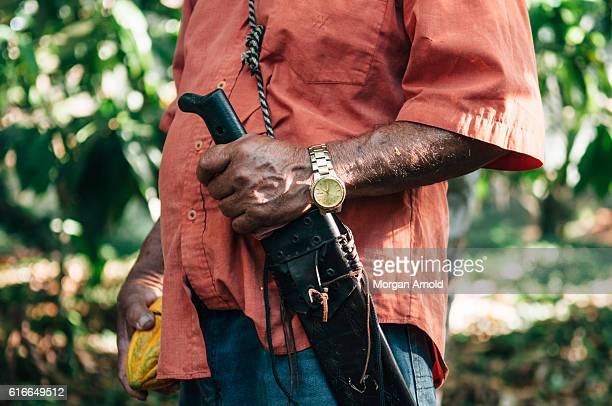 A cacao farmer holds a cacao pod in one hand and his machete in the other