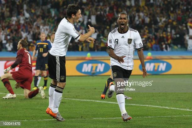 Cacau of Germany celebrates scoring his side's fourth goal with team mate Mesut Oezil during the 2010 FIFA World Cup South Africa Group D match...