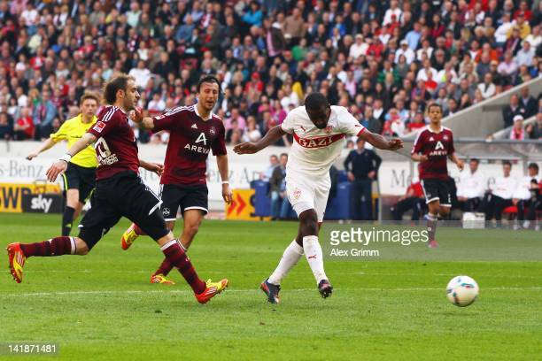Cacau of Stuttgart scores his team's first goal against Dominic Maroh and Javier Pinola of Nuernberg during the Bundesliga match between VfB...