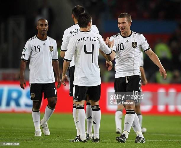 Cacau, Sascha Riether and Lukas Podolski celebrate the 6-1 victory after the EURO 2012 Group A Qualifier match between Germany and Azerbaijan at...