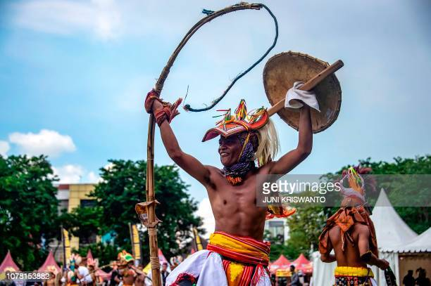 A Caci fighter gestures with his whip and shield during a duel in Surabaya East Java province on January 6 2019 Caci a martial art that uses whips...