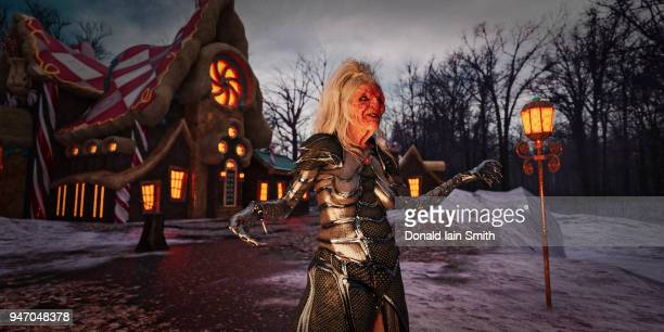cackling witch wearing fantasy armor standing before candy house - ugly witches stock photos and pictures