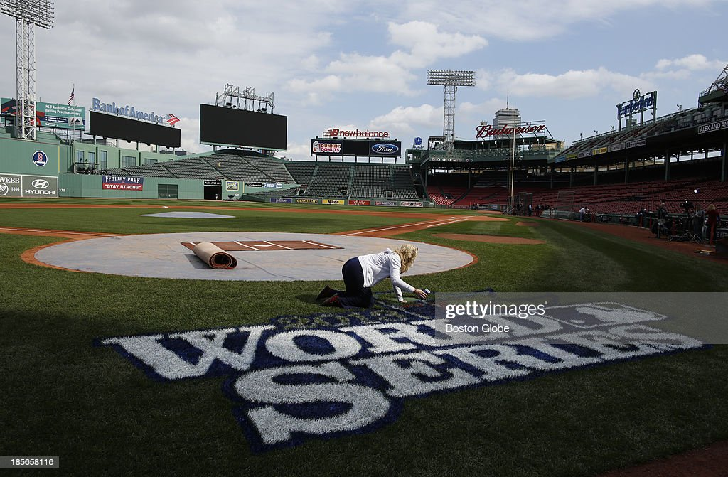Cacky Mellor sprinkles glitter on the World Series logo at Fenway Park in Boston, Oct. 22, 2013.