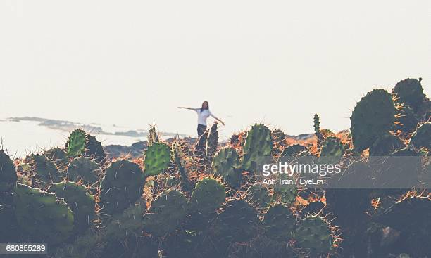 Cactuses Against Woman With Arms Outstretched Standing By Sea