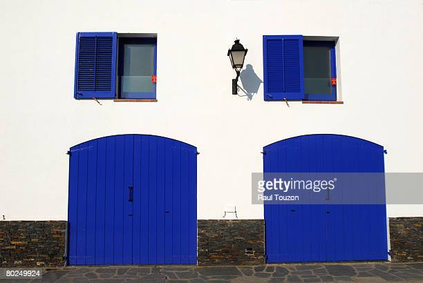 A white house with blue shutters and doors.