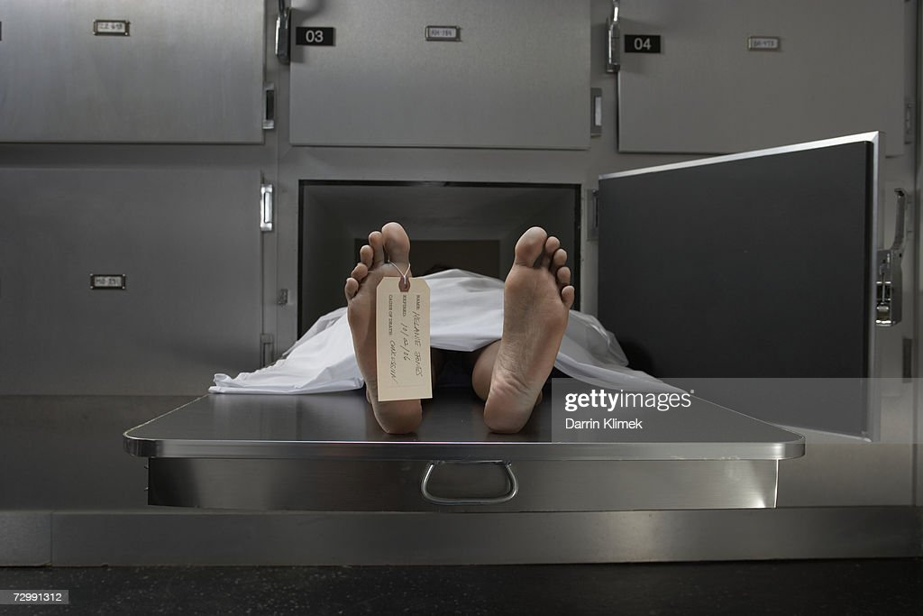 Cadaver on autopsy table, label tied to toe : Stock Photo