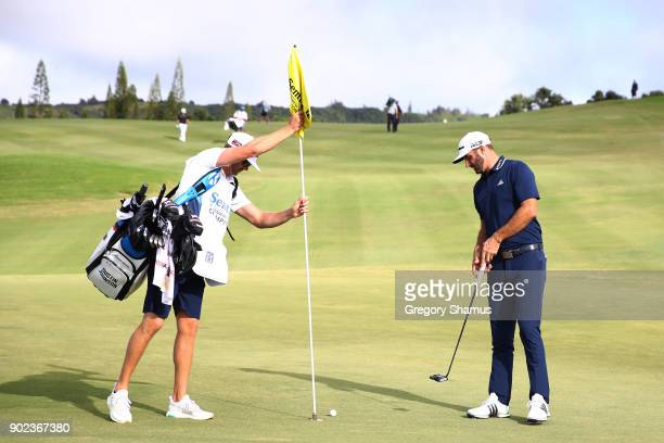 Caddie Austin Johnson pulls the pin flag as Dustin Johnson of the United States prepares to tap in for eagle on the 12th green during the final round...