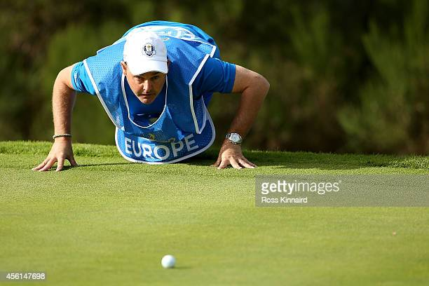 Caddie Billy Foster lines up a putt during the Afternoon Foursomes of the 2014 Ryder Cup on the PGA Centenary course at the Gleneagles Hotel on...