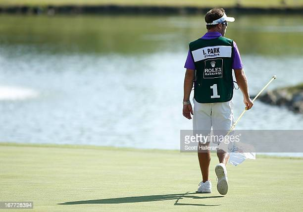 Caddie Brad Beecher walks across the 18th green during the final round of the 2013 North Texas LPGA Shootout at the Las Colinas Counrty Club on April...