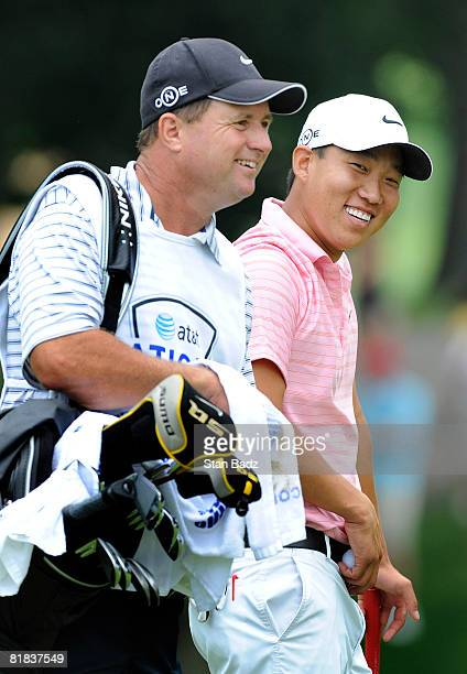 Caddie Eric Larson and Anthony Kim wait for play at the second tee box during the final round of the ATT National held on the Blue Golf Course at...