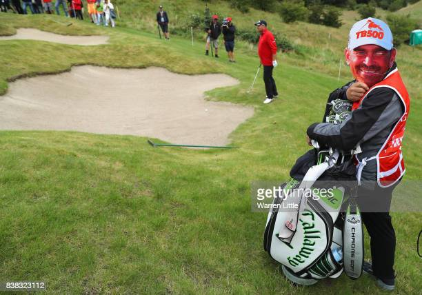 Caddie for Thomas Bjorn of Denmark marks his 500th European Tour appearance by doning look a like face mask on the 16th green during the first round...
