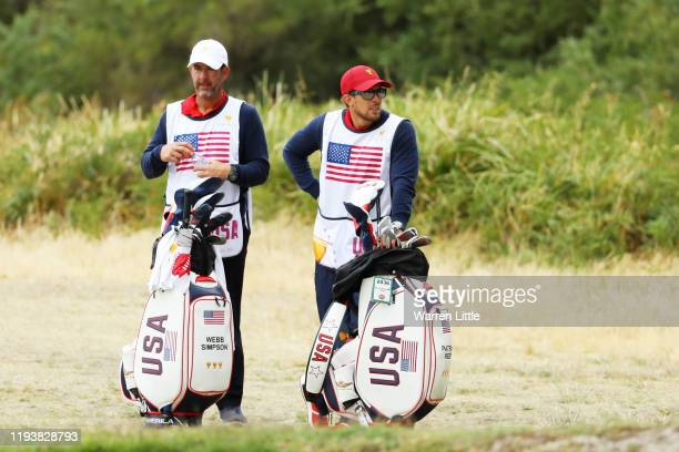 Caddie for Webb Simpson of the United States team, Paul Tesori, and caddie of Patrick Reed of the United States team, Kessler Karain, look on during...