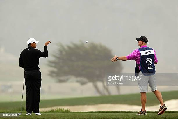 Caddie Joe LaCava tosses a golf ball to Tiger Woods on the tee for the 12th hole during the second round of the ATT Pebble Beach National ProAm at...