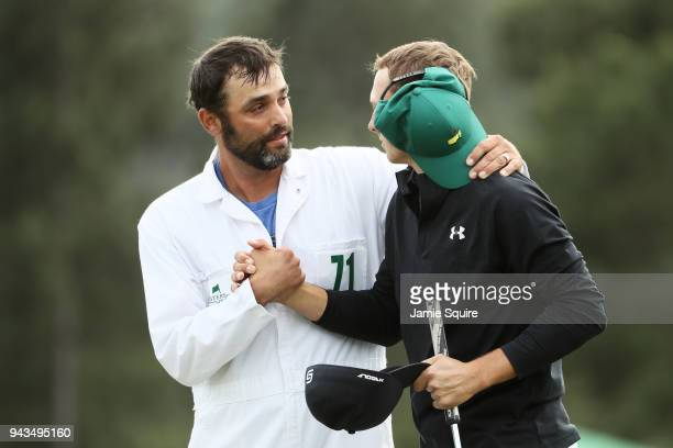 Caddie Michael Greller and Jordan Spieth of the United States shake hands on the 18th green during the final round of the 2018 Masters Tournament at...