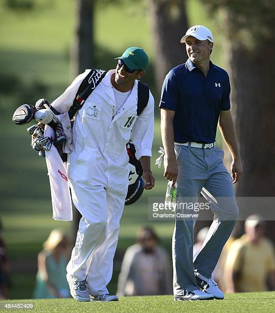 Caddie Michael Greller and Jordan Spieth smile at golfer Adam Scott as they walk up the 15th fairway during the third round at the Masters Tournament...