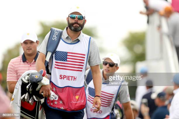 Caddie Michael Greller, Patrick Reed and caddie Kessler Karain walk the course during the second round of the Presidents Cup at Liberty National Golf...