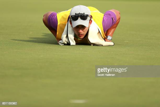 Caddie of Patrick Reed of the United States Kessler Karain lines up a putt during the final round of the 2017 PGA Championship at Quail Hollow Club...