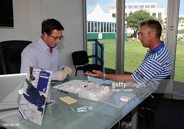 Caddie Phil Morbey under goes a cholesterol test with a consultant from the road to health company after the pro am before the Portugal Masters at...
