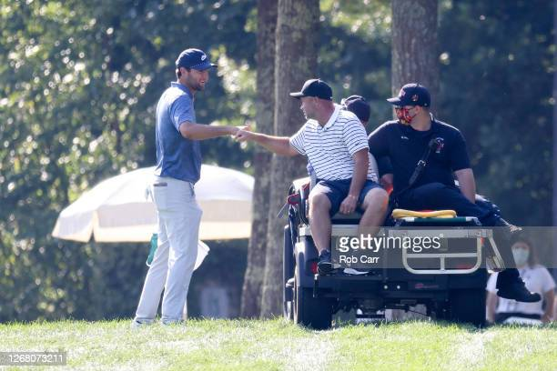 Caddie Scotty Macguiness fist bumps Scottie Scheffler of the United States as he leaves the course on a golf cart due to an injury during the final...