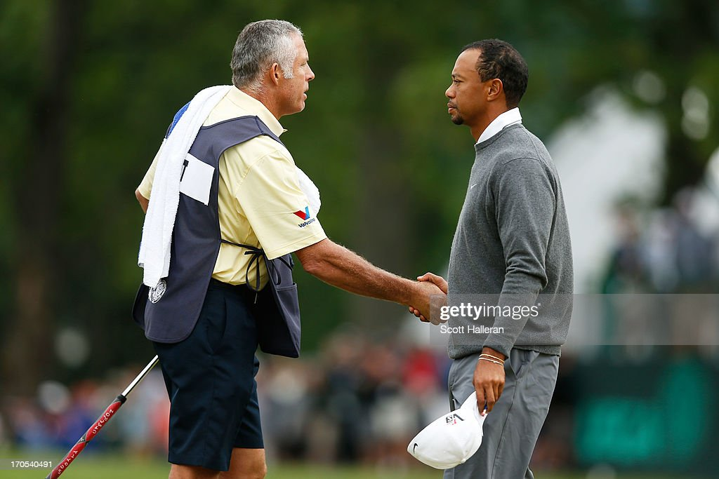 Caddie Steve Williams and Tiger Woods of the United States shake hands on the 18th green during a continuation of Round One of the 113th U.S. Open at Merion Golf Club on June 14, 2013 in Ardmore, Pennsylvania.
