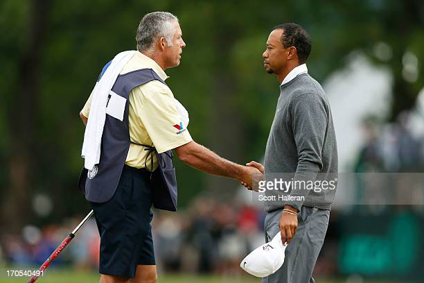 Caddie Steve Williams and Tiger Woods of the United States shake hands on the 18th green during a continuation of Round One of the 113th U.S. Open at...