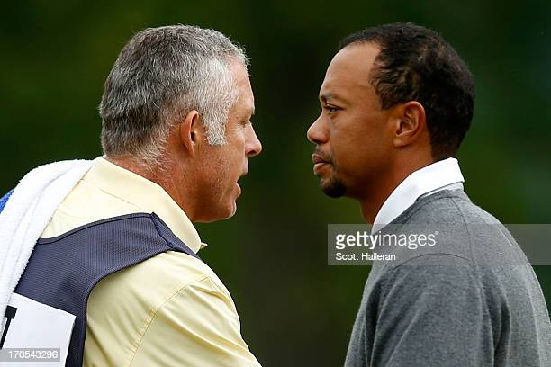 Caddie Steve Williams and Tiger Woods of the United States walk past one another on the 18th green during a continuation of Round One of the 113th...