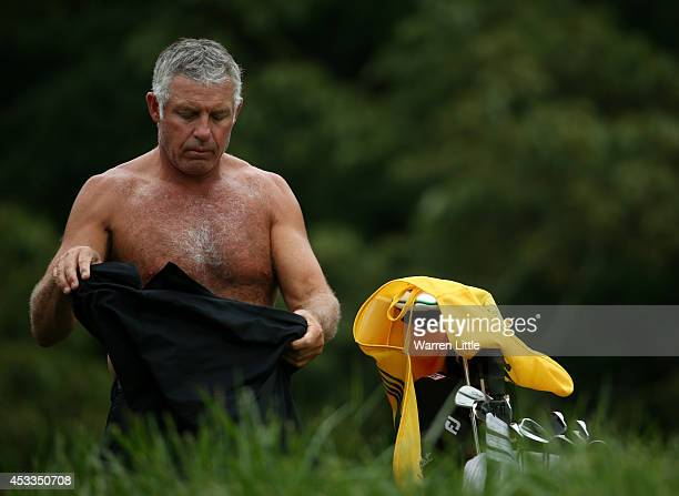 Caddie Steve Williams changes his shirt on the fourth tee during the second round of the 96th PGA Championship at Valhalla Golf Club on August 8 2014...