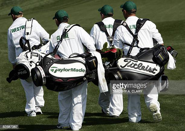 Caddies for golfers Lee Westwood Darren Clarke Thomas Bjorn and Davis Love walk down the first fairway 04 April 2005 during the opening practice...